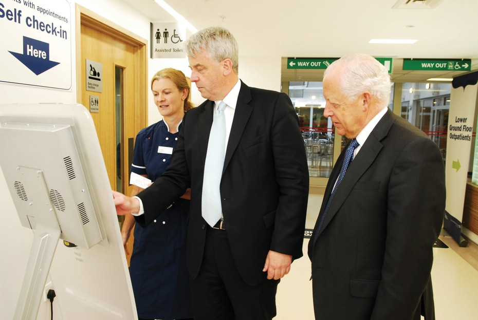Mr Lansley uses one of the self check-in kiosks with Jo Pierre (Nurse Manager) and Professor Sir Christopher Edwards (Chairman)